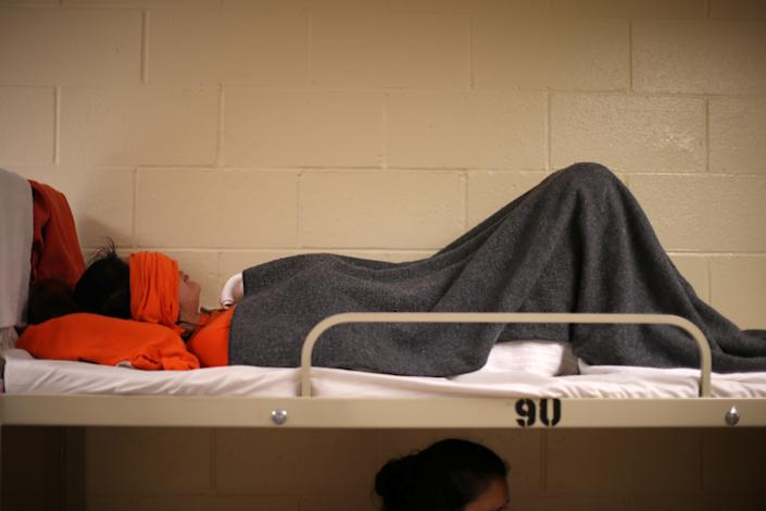 A woman lies on a bed in a dormitory at the Adelanto immigration detention center