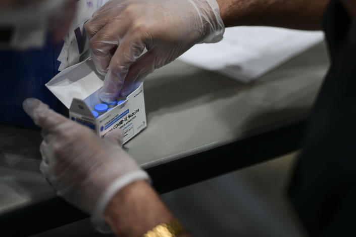 A health worker breaks out a box of COVID 19 vaccine during a mass vaccination event carried out by the Department of Health and the Voces nonprofit organization, at the Miramar Convention Center in San Juan, Puerto Rico, Wednesday, March 31, 2021. (AP Photo/Carlos Giusti)