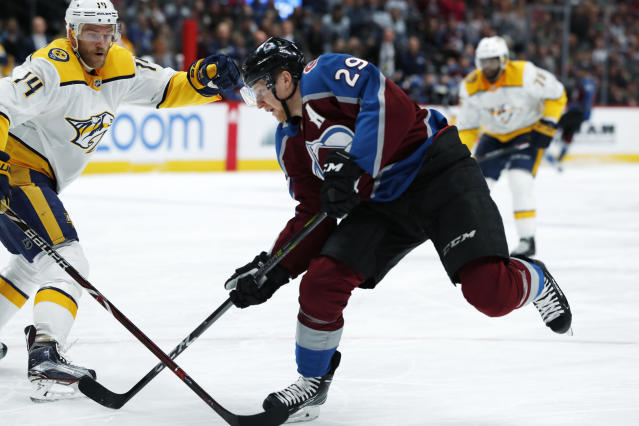 Colorado Avalanche center Nathan MacKinnon, front, fires the puck past Nashville Predators defenseman Mattias Ekholm during the first period of an NHL hockey game Friday, March 16, 2018, in Denver. (AP Photo/David Zalubowski)