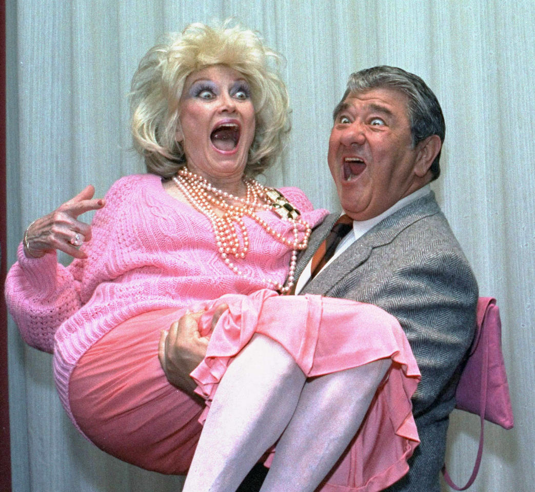 FILE-In this Oct. 9, 1985, file photo, Comedian Phyllis Diller gets a lift from emcee Buddy Hackett prior to the celebrity stag luncheon roast at the New York Friars Club in New York City. Diller, the housewife turned humorist who aimed some of her sharpest barbs at herself, died Monday, Aug. 20, 2012, at age 95 in Los Angeles.(AP Photo/Marty Lederhandler, File)
