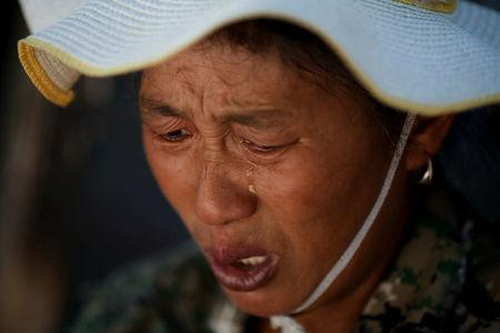 Wang Jun reacts as she talks about her life as a migrant worker at Dongsanqi village in the outskirts of Beijing