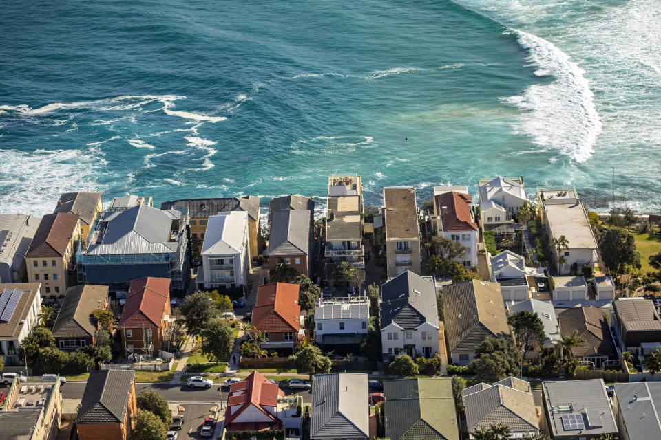 Aerial photography of houses and apartments on coastline with ocean, surf, waves. Brighton Blvd, Ramsgate Ave, North Bondi, Sydney, Australia