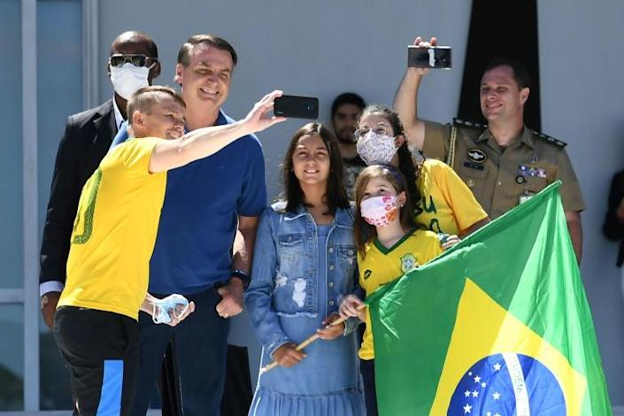 Brazilian President Jair Bolsonaro and his daughter Laura (C) pose for a selfie with supporters outside his residence in Brasilia on Sunday (AFP Photo/EVARISTO SA)