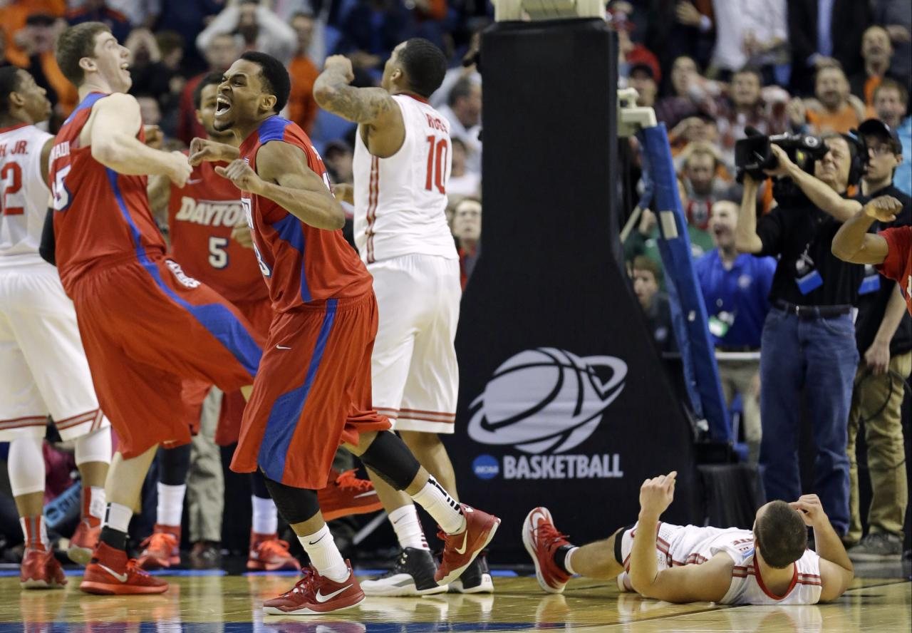 Dayton's Vee Sanford, fourth from left, and Matt Kavanaugh, second from left, react after Ohio State's Aaron Craft, right, missed the final shot of the second half of a second-round game in the NCAA college basketball tournament in Buffalo, N.Y., Thursday, March 20, 2014. Dayton won 60-59. (AP Photo/Frank Franklin II)