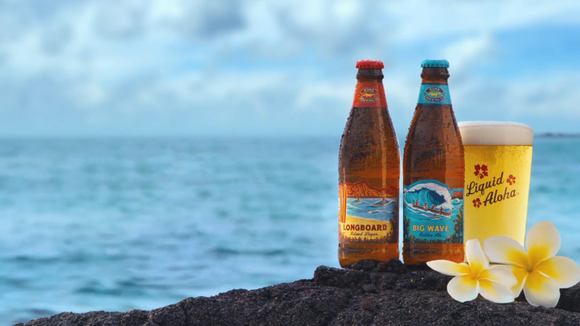 Kona beer bottles and glass are positioned near the ocean