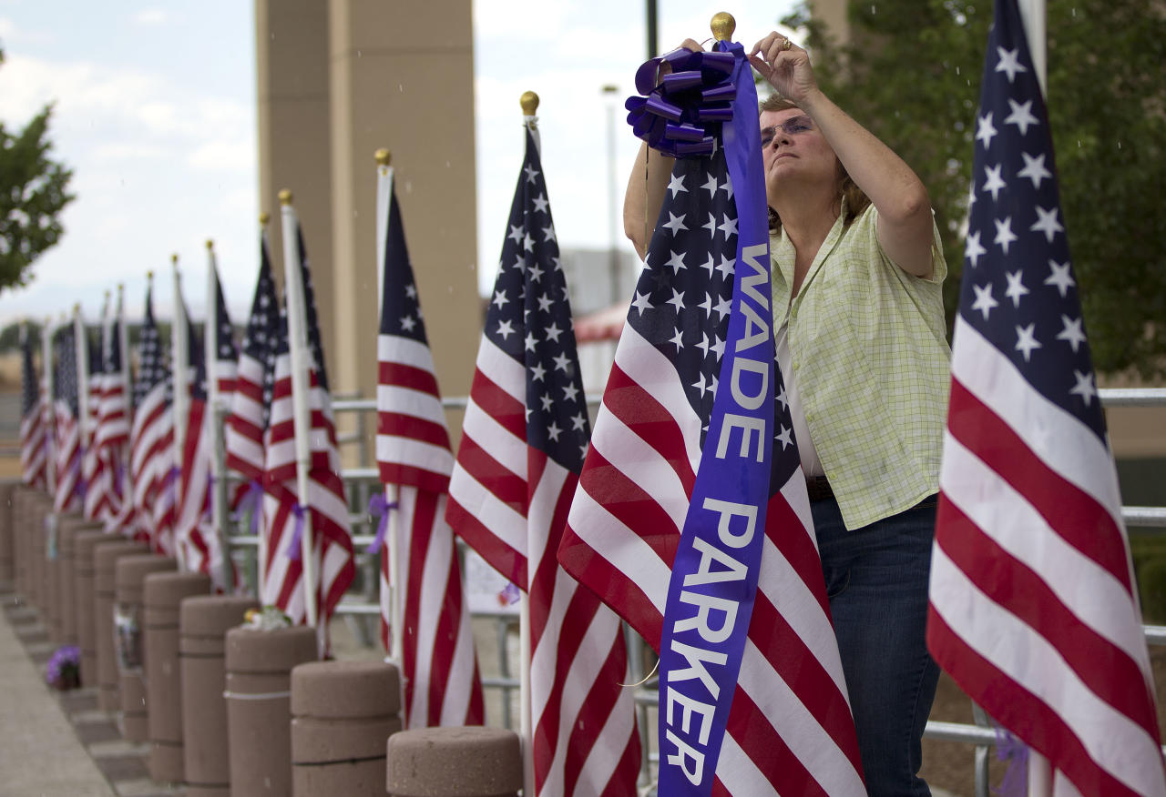 Patty Brookins, director of human resources for the Central Yavapai Fire Department, ties purple ribbons and banners with the names of each of the 19 fallen Granite Mountain Hotshot firefighters to 19 United States flags outside Tim's Toyota Center, Monday, July 8, 2013 in Prescott, Ariz. A memorial service will be held Tuesday during which firefighters from across the nation will join with the men's families, Vice President Joe Biden and other dignitaries to honor the firefighters who were killed June 30 battling a blaze near Yarnell, Ariz. (AP Photo/Julie Jacobson)