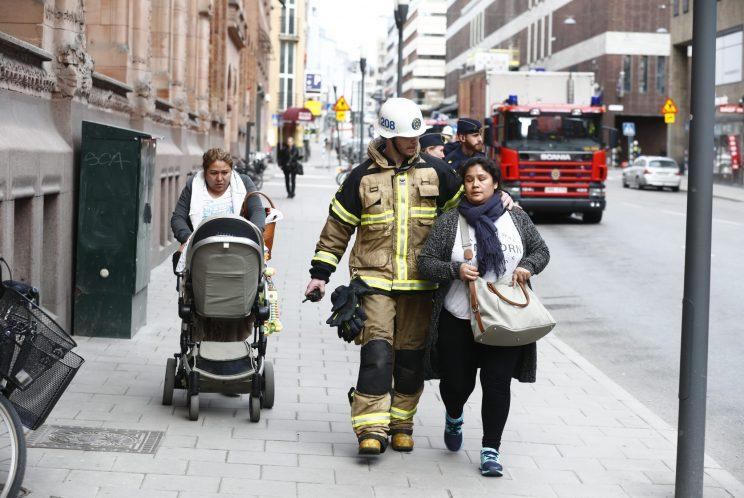 Emergency service workers help people in Stockholm (Rex)