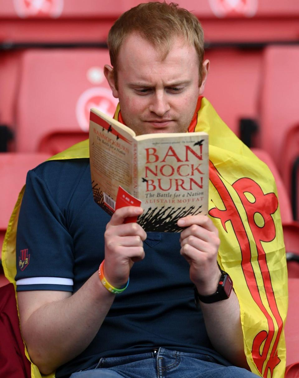 A fan reading a book about Bannockburn - Stu Forster/Getty Images