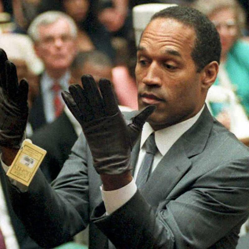 OJ Simpson looks at a new pair of Aris extra-large gloves that prosecutors had him put on during his double-murder trial in Los Angeles in 1995. - Credit: AFP