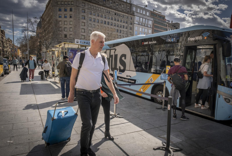 A tourist holding a suitcase heads to the AeroBus stop bound for Barcelona's Prat airport on March 1, 2020. (Paco Freire/SOPA Images/LightRocket via Getty Images)