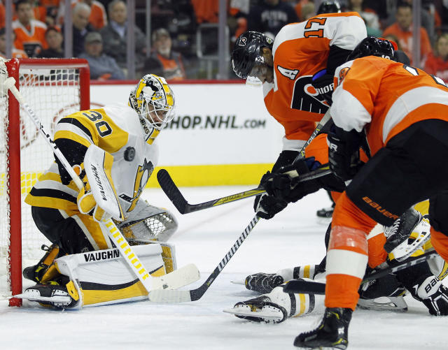 Pittsburgh Penguins goalie Matthew Murray, left, stops a shot as Philadelphia Flyers' Wayne Simmonds, center, and Nolan Patrick, look for a rebound during the second period in Game 4 of an NHL first-round hockey playoff series Wednesday, April 18, 2018, in Philadelphia. (AP Photo/Tom Mihalek)