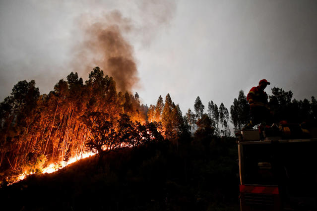 <p>A firefighter stands on top of a fire truck during a wildfire in Penela, Coimbra, central Portugal, June 18, 2017. (Patricia De Melo Moreira/AFP/Getty Images) </p>