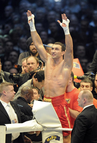 Heavyweight world boxing champion Wladimir Klitschko of Ukraine, center, celebrates after he knocked out Jean-Marc Mormeck of France in the 4th Round of their WBA, IBF, WBO and IBO title bout in Duesseldorf, Germany, Saturday, March 3, 2012. (AP Photo/Martin Meissner)