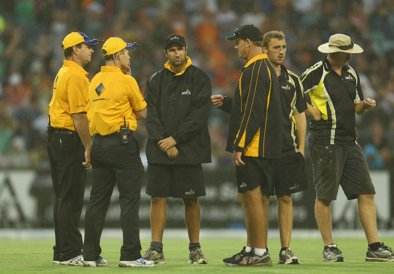 PERTH, AUSTRALIA - JANUARY 16: The umpires have a discussion with the groundsmen as rain delays play during the Big Bash League semi-final match between the Perth Scorchers and the Melbourne Stars at the WACA on January 16, 2013 in Perth, Australia.  (Photo by Robert Cianflone/Getty Images)