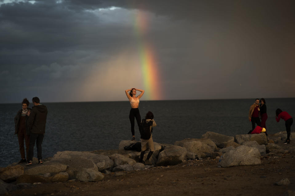 People pose as they are photographed in front of a rainbow, following a storm in Barcelona, Spain, Saturday, Jan. 30, 2021. (AP Photo/Emilio Morenatti)