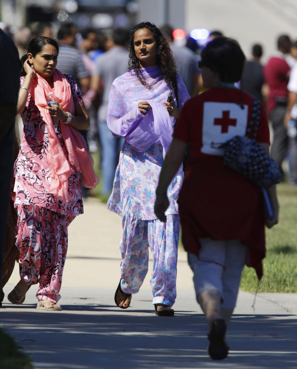 Woman walk with a red cross worker outside the Sikh Temple in Oak Creek, Wi, where a shooting took place Sunday, Aug 5, 2012. At least six people were killed Sunday when a gunman opened fire the Milwaukee-area temple, and the suspected shooter later died in an exchange of gunfire with police, authorities said. (AP Photo/Jeffrey Phelps)