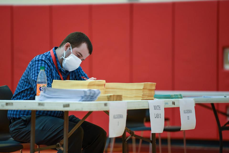 North College Hill High School Math teacher, Jason Gregory, 33, grades papers as he waits for students to come pick up their packets so they can continue their schooling form home during the COVID-19 pandemic.