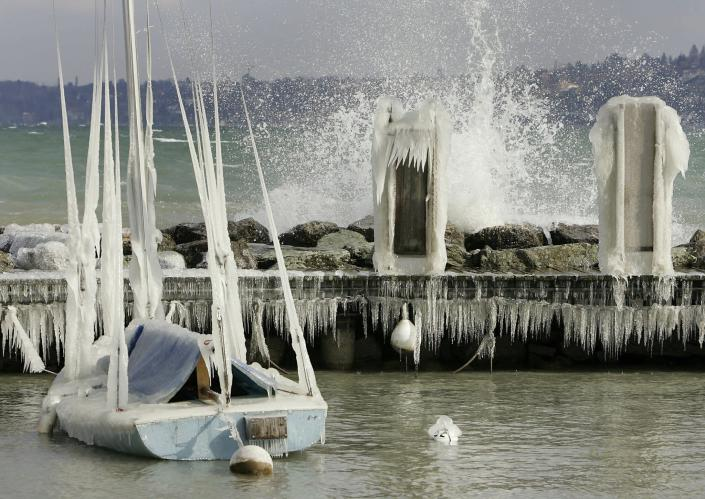 FILE - In this Monday, Feb. 28, 2005 file photo, a boat coated with ice lies at an embankment of lake Geneva, Switzerland. A cold north east wind came up on Monday and brought temperatures of down to minus 20 degrees centigrade (minus 4 Fahrenheit). On Friday, Feb. 19, 2021, The Associated Press reported on a photo circulating online incorrectly asserting it shows boats covered with ice in a marina in Galveston, Texas, during this week's record freeze. The scene was actually from Lake Geneva from the 2015 storm in pictured in this similar photo. (Martial Trezzini/Keystone via AP)