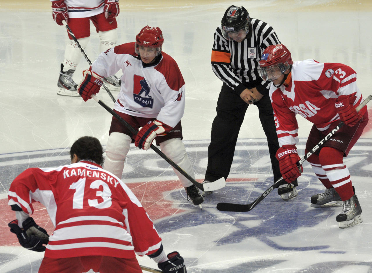 Russia's President Vladimir Putin (L, top), Governor of Moscow Region Sergei Shoigu (R) and former player Valeri Kamensky take part in the All-Russian ice hockey festival among amateur teams at Megasport Arena in Moscow, May 7, 2012. Putin played for a team representing the Russian Amateur Ice Hockey League, which competed with the Russian Legends Team.  REUTERS/Aleksey Nikolskyi/RIA Novosti/Pool
