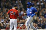 Toronto Blue Jays' Teoscar Hernandez, right, scores on a single by Randal Grichuk off Boston Red Sox's Colten Brewer (54) during the seventh inning of a baseball game in Boston, Friday, June 21, 2019. (AP Photo/Michael Dwyer)