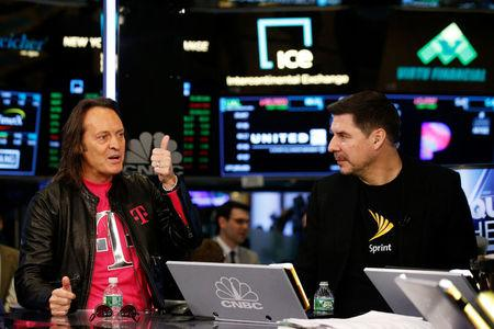 T-Mobile CEO John Legere speaks as Sprint CEO Marcelo Claure looks on at the New York Stock Exchange in New York