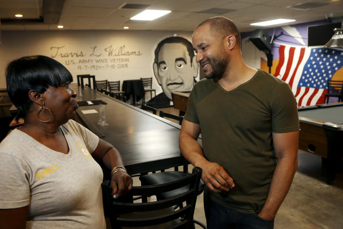 """In this Tuesday, July 30, 2019 photo, activist Lawrence Robinson, right, talks with Jeanette Murphy, at the Post 65 American Legion hall, formed during the era of segregation and recently renovated in Phoenix. Three American Legion posts stand within miles of each other in central Phoenix, a curious reminder of how segregation once ruled the U.S. Southwest as well as the Deep South. Post 65 draws a largely black crowd. """"It's affordable, and there is camaraderie,"""" said Robinson, who attends legion events with friends. (AP Photo/Ross D. Franklin)"""