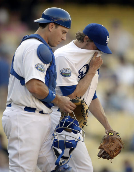 Los Angeles Dodgers starting pitcher John Ely, right, covers his face as catcher A.J. Ellis looks on after Ely walked in a run in the 12th inning of a baseball game against the St. Louis Cardinals, Sunday, Sept. 16, 2012, in Los Angeles. (AP Photo/Mark J. Terrill)