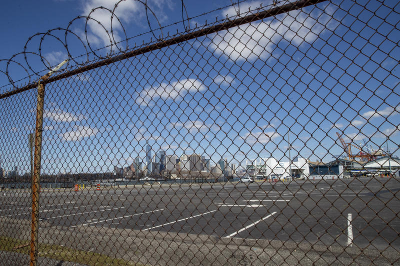 The Manhattan skyline is seen behind the parking lot and terminal of the Brooklyn Cruise Terminal, Thursday, April 2, 2020 in New York. N.Y. New York Gov. Governor Andrew Cuomo announced last week that the terminal with be transformed into a temporary field hospital to increase New York's hospital capacity while cases of the coronavirus skyrocket. (AP Photo/Mary Altaffer)