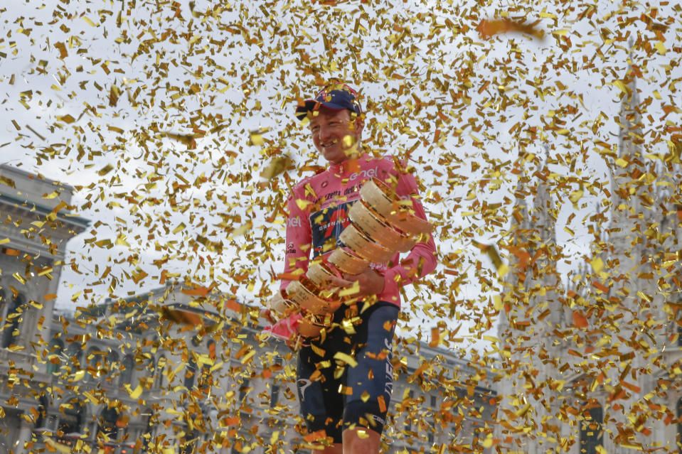 Britain's Tao Geoghegan Hart holds the trophy after winning the Giro d'Italia cycling race, in Milan, Italy, Sunday, Oct. 25, 2020. In one of the most exciting final stages of a Grand Tour, British rider Tao Geoghegan Hart won the Giro d'Italia on Sunday, edging out Australian Jai Hindley by just 39 seconds. (AP Photo/Luca Bruno)