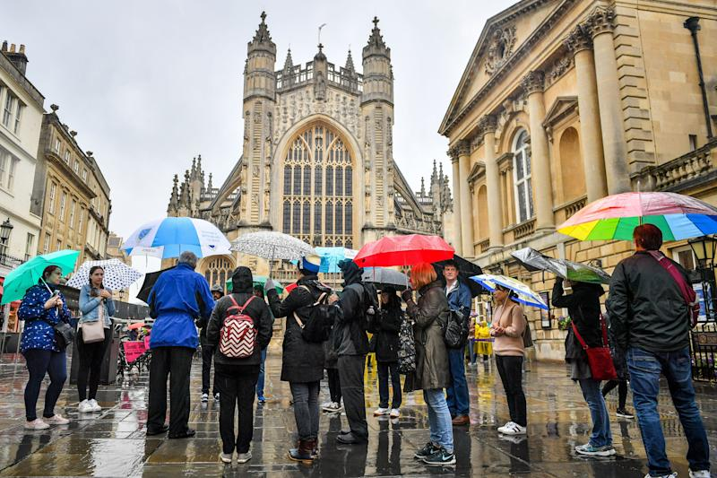 Tourists using umbrellas in Bath (Photo by Ben Birchall/PA Images via Getty Images)
