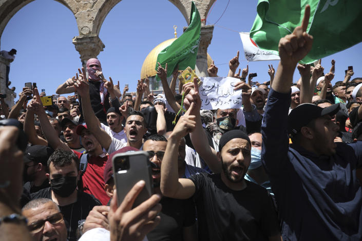 Worshippers chant slogans and wave Hamas flags during a protest against the likely evictions of Palestinian families from the homes, after the last Friday prayers of the Muslim holy month of Ramadan at the Dome of the Rock Mosque in the Al Aqsa Mosque compound in the Old City of Jerusalem, Jerusalem, Friday, May 7, 2021. (AP Photo/Mahmoud Illean)