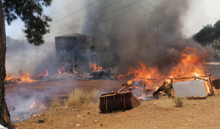 A wildfire fanned by strong winds engulfs a building near the Mediterranean coastal town of Manavgat, Antalya, Turkey, Wednesday, July 28, 2021. Authorities evacuated homes in Manavgat as a wildfire raged Wednesday through a forest. Gendarmerie forces helped move residents out of four neighborhoods in the town out of the fire's path as firefighters worked to control the blaze, the Manavgat district governor Mustafa Yigit told the state-run Anadolu Agency. (Arif Kaplan/IHA via AP)