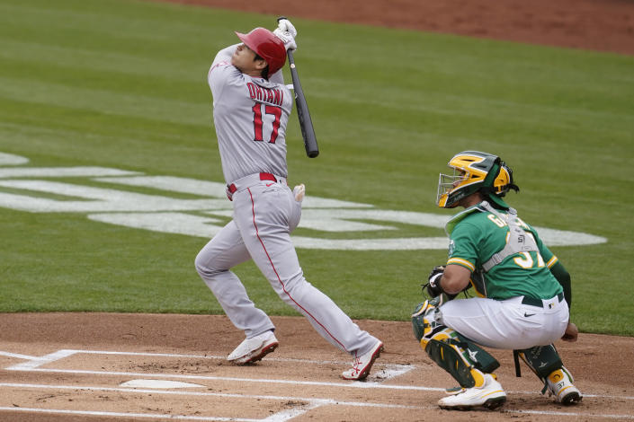 Los Angeles Angels designated hitter Shohei Ohtani (17) watches his flyout in front of Oakland Athletics catcher Aramis Garcia during the first inning of a baseball game in Oakland, Calif., Saturday, May 29, 2021. (AP Photo/Jeff Chiu)