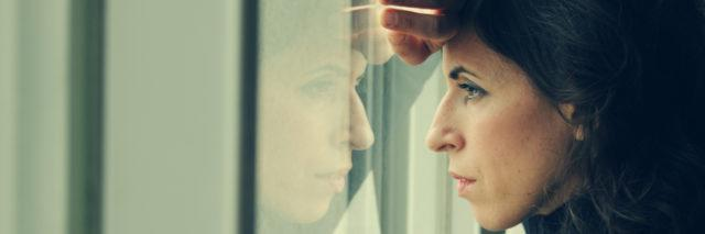 A woman stares intensely out of a window.