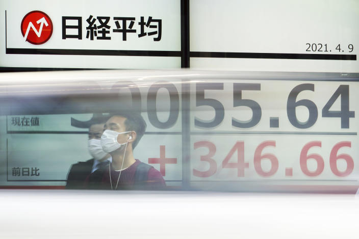 Men wearing protective masks stand in front of an electronic stock board showing Japan's Nikkei 225 index at a securities firm as a car passes by in Tokyo Friday, April 9, 2021. Shares fell Friday in most Asian markets after China reported a stronger than expected rise in prices that could prompt authorities to act to cool inflation. (AP Photo/Eugene Hoshiko)