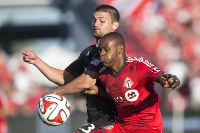 Toronto FC 's Jackson Goncalves, right, battles for the ball with D.C. United's Perry Kitchen during the first half of an MLS soccer game in Toronto on Saturday, July 5, 2014. (AP Photo/The Canadian Press, Chris Young)