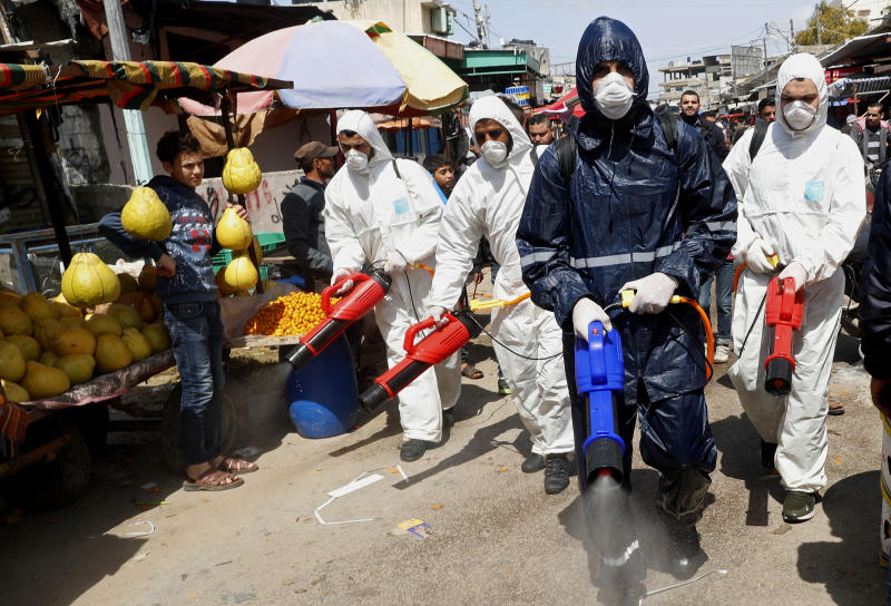 Workers wearing protective gear spray disinfectant as a precaution against the coronavirus, at the main market in Gaza City, Thursday, March 19, 2020. The Middle East has some 20,000 cases of the virus, with most cases in Iran or linked to travel from Iran. The vast majority of people recover from COVID-19. (AP Photo/Adel Hana)