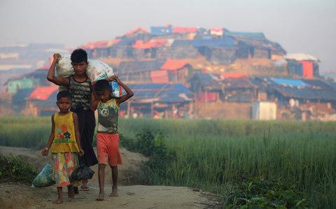 Rohingya refugee children carry supplies through Balukhali refugee camp near Cox's Bazar - Credit:  HANNAH MCKAY/Reuters