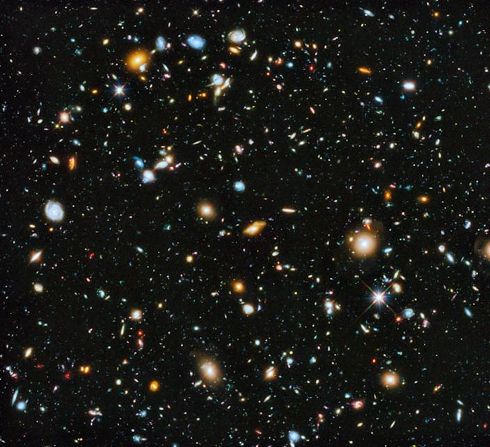 A black square of deep space is dotted with galaxies, stars and other celestial objects with various sizes, shapes, and colors.