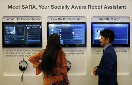 An attendee communicate with SARA, a socially aware robot assisstant, during a presentation at the annual meeting of the World Economic Forum (WEF) in Davos, Switzerland, January 17, 2017. REUTERS/Ruben Sprich