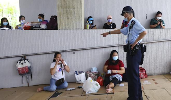 Police officers in Central remind domestic helpers of tightened anti-pandemic rules limiting public gatherings to two people earlier this month. Photo: Dickson Lee