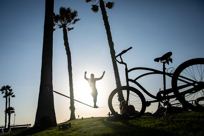 """Damien Arredondo walks the slack line, while Cory Babinski takes a breather during their workout at Noble Park in Hermosa Beach. <span class=""""copyright"""">(Jay L. Clendenin/Los Angeles Times)</span>"""