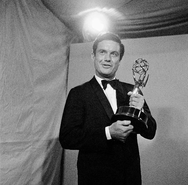 """FILE - In this May 22, 1966 file photo, actor Cliff Robertson holds the Emmy he won for the outstanding single performance by an actor in a leading role in a drama at the 18th annual Television Academy Awards in the Hollywood section of Los Angeles. Robertson, the movie actor who played John F. Kennedy in """"PT-109,"""" won an Oscar for """"Charly"""" and was famously victimized in a 1977 Hollywood forgery scandal, died Saturday, Sept. 10, 2011. He was 88. (AP Photo)"""