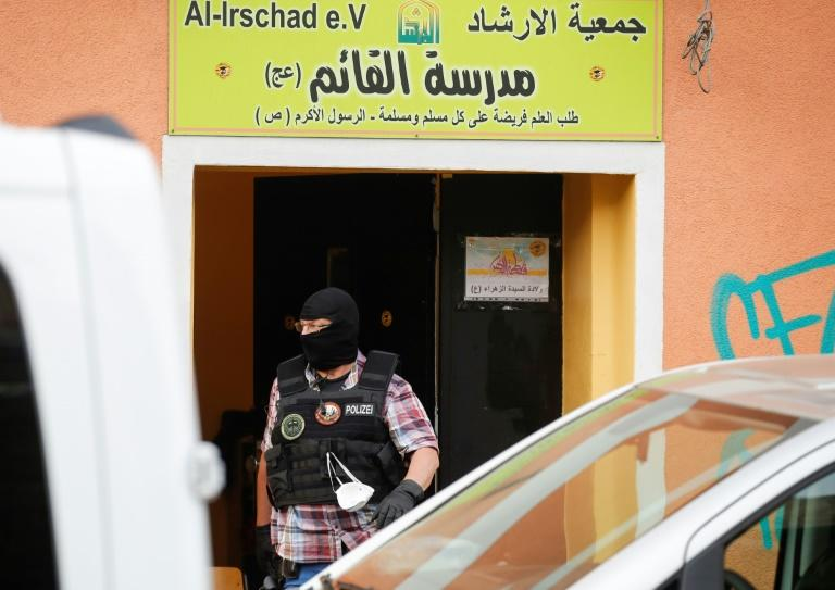 A police officer walks out of Al-Irschad Mosque during a raid in Berlin, as dozens of police and special forces stormed mosques and associations linked to Hezbollah in Bremen, Berlin, Dortmund and Muenster early Thursday. (AFP Photo/Odd ANDERSEN)