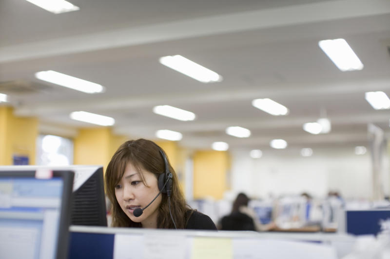 Woman talking with headset in front PC in office