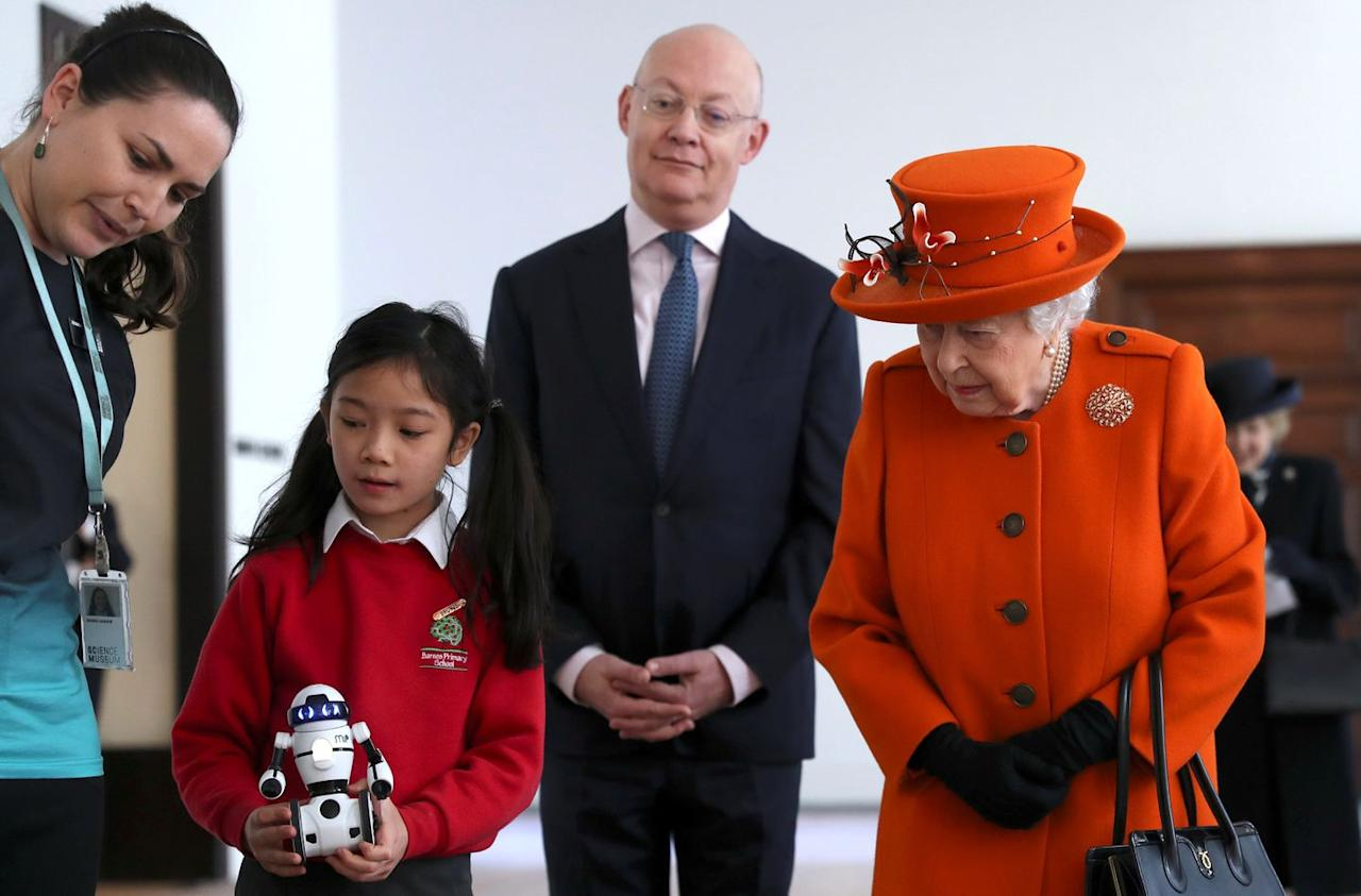 <p>A child shows the Queen a small robot, as the Science Museum's director looks on.</p>