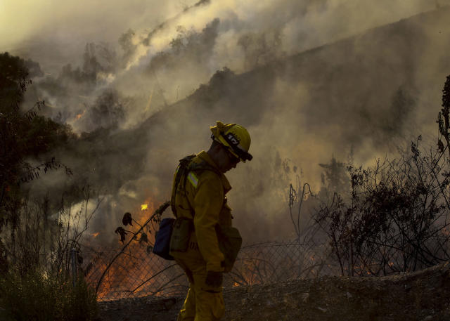 <p>A firefighter keeps watch a wildfire along a hillside in Azusa, Calif., Monday, June 20, 2016. Police in the city of Azusa and parts of Duarte ordered hundreds of homes evacuated. Others were under voluntary evacuations. (AP Photo/Ringo H.W. Chiu) </p>