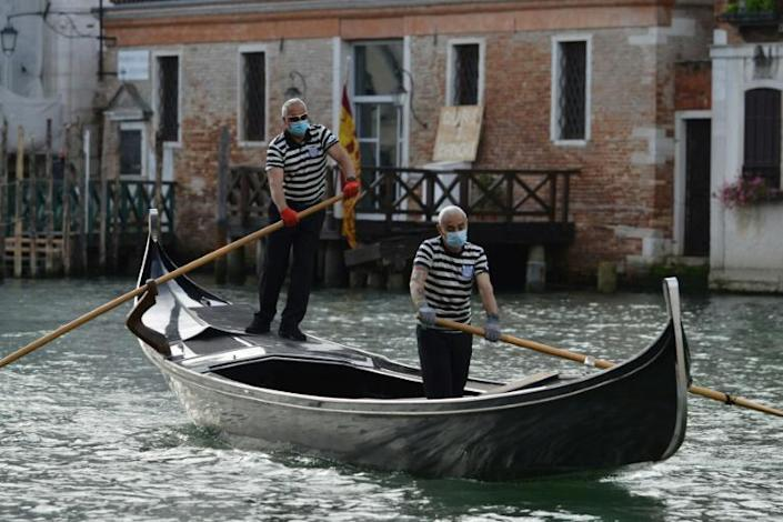 Gondoliers returned to the canals of Venice, even if they are now wearing masks and gloves (AFP Photo/ANDREA PATTARO)