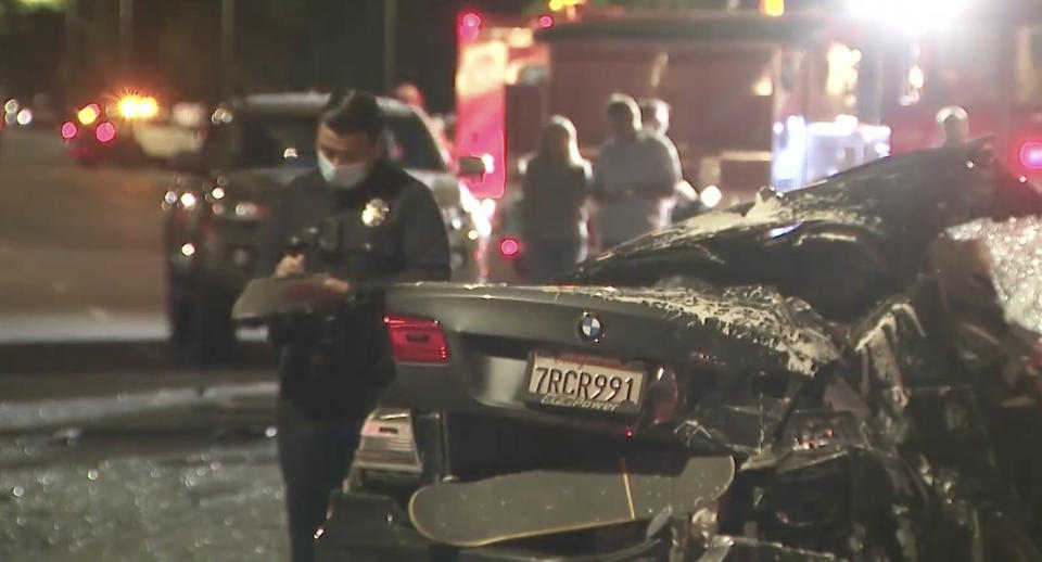 The smashed BMW at the LA scene with a police officer seen in the background.