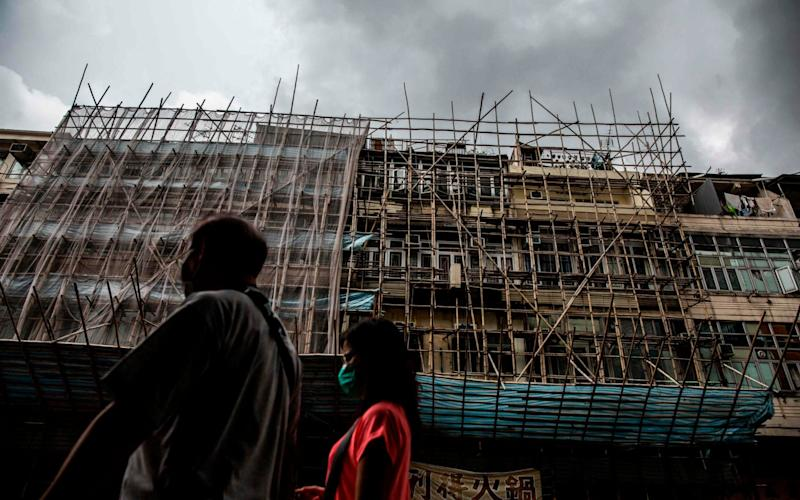 A couple walk past bamboo scaffolding on a building in Kowloon City, Hong Kong today. - Isaac Lawrence/AFP